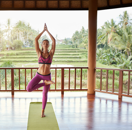 joined: Full length shot of young woman doing yoga exercise tree pose. Fitness woman standing on one leg with hands joined overhead.