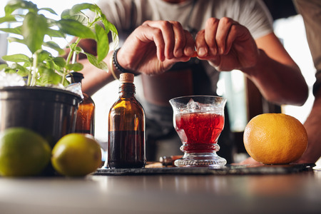 Close-up shot van barman handen voorbereiding Negroni cocktail met grapefruit. Hij zet wat essentie uit de grapefruithuid in het cocktailglas op de balie.
