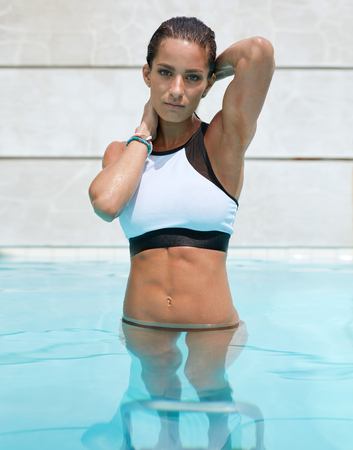 Portrait of beautiful young female in swimming pool looking at camera with her hands in hair. Muscular young woman in swimwear enjoying swimming in pool outdoors.