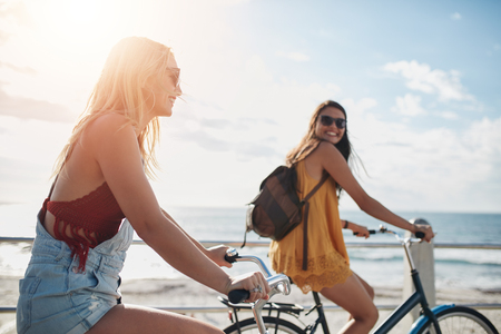 cycles: Dos amigos femeninos que montan ciclos en el paseo marítimo. las mujeres jóvenes felices disfrutando de montar las bicicletas en un día de verano.