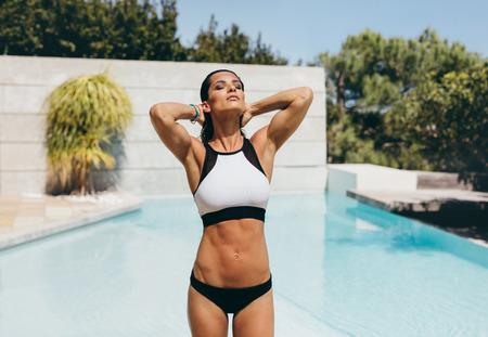 traje de baño: Tiro al aire libre de una atractiva joven posando en un bikini junto a una piscina. Mujer atleta en traje de baño de pie con las manos detrás de la cabeza.