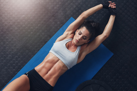 Overhead shot of muscular and fit young woman doing stretching workout exercise mat. Fitness female lying on mat with stretching her hands. Banque d'images