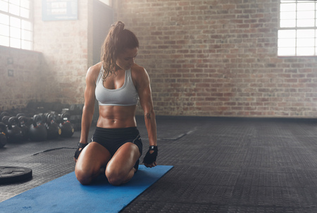 Shot of fitness woman sitting on exercise mat and looking at her triceps. Muscular woman working out at the fitness club. Stock Photo