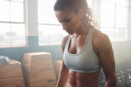 Close up shot of muscular woman standing in the gym and looking down. She is wearing a sports bra. Female model taking a break from her training.