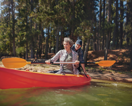 adventure: Portrait of happy mature couple having fun at the lake. Woman paddling kayak with man pushing from behind on a summer day.