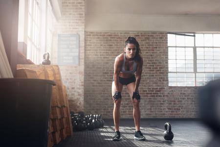 Crossfit ジムで自信を持って若い女性の完全な長さのショット。両手を膝の上に立っている筋肉スポーツウーマンは彼女のフィットネス トレーニング
