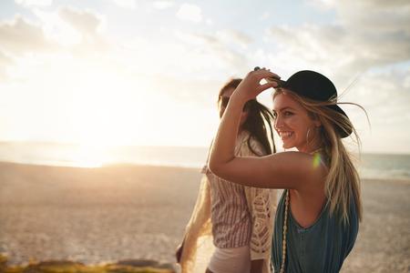 Schöne Freunde, die einen Spaziergang am Strand an einem sonnigen Tag zu genießen. Zwei junge Frauen, die zusammen an einem Strand zu Fuß.