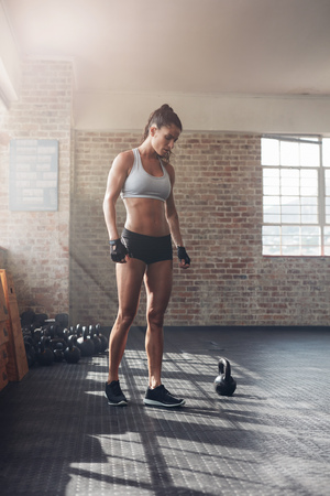 tough woman: Full length shot of strong young woman in sportswear standing in gym. Tough female athlete at crossfit gym. Stock Photo