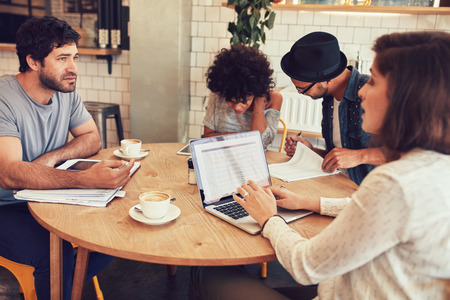 Team of creative people sitting at a cafe with some documents and laptop. Young men and women in coffee shop for business meeting.