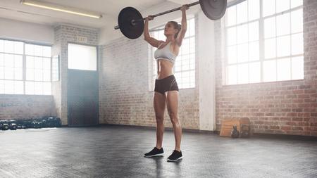 Imagen de la longitud completa de mujer joven y fuerte ejercicio con pesas. atleta hembra levantar objetos pesados. Foto de archivo