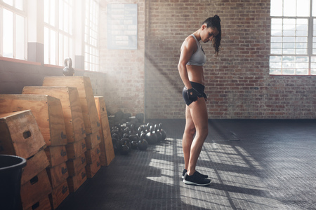tough woman: Full length indoor shot of determined young woman standing in gym. Tough female athlete at crossfit gym with exercise equipments on floor. Stock Photo