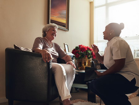 Home caregiver talking with a senior woman sitting on chair at home. Female nurse visiting senior female patient home for routine checkup. Stock Photo