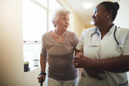 医療従事者と一緒に歩く年配の女性の肖像画。特別養護老人ホームを歩きながら支援シニア女性患者を看護師します。 写真素材