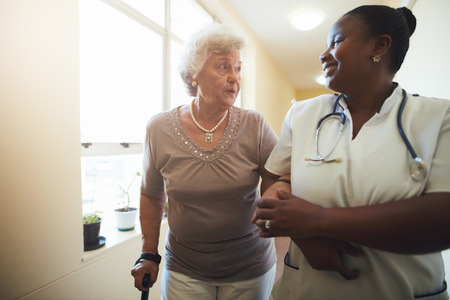 Portrait of healthcare worker and senior woman walking together. Nurse assisting senior female patient while walking in nursing home.