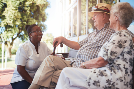age old: Portrait of senior couple relaxing on a bench outside their retirement home. Caucasian elderly man and woman sitting with female nurse at old age home.