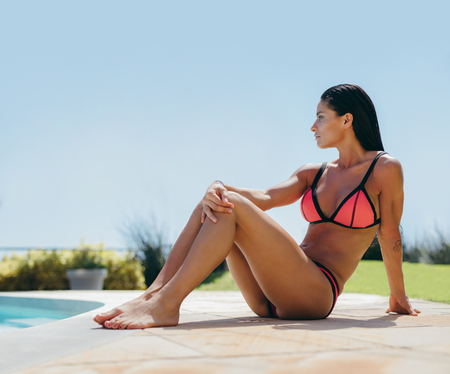 bikini pool: Outdoor shot of attractive woman in bikini relaxing near swimming pool. Beautiful young female at poolside looking away. Stock Photo