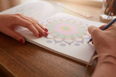 female hands: Close up of female hands drawing in adult coloring book at home.