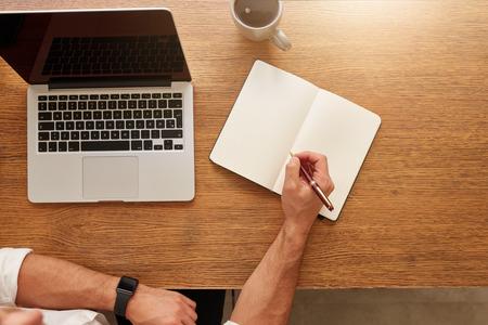 hombre escribiendo: Cerca del hombre de escribir notas en el cuaderno personal con un ordenador portátil y una taza de café en la mesa.