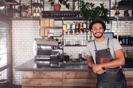 Portrait de jeune homme debout au comptoir dans son café. Café travaillant en tablier et chapeau souriant à la caméra.
