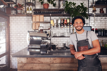 Portrait of young man standing at the counter in his cafe. Coffee shop working in apron and hat smiling at camera. Reklamní fotografie