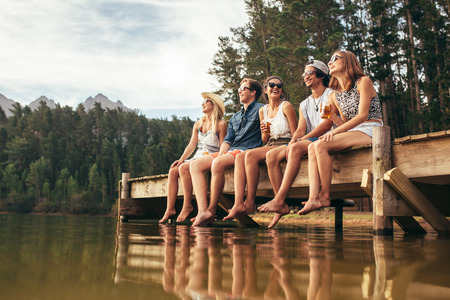 Group of happy young friends having fun and drinking beer while sitting on the jetty at the lake. Young men and woman enjoying a day on Lake. Stock Photo