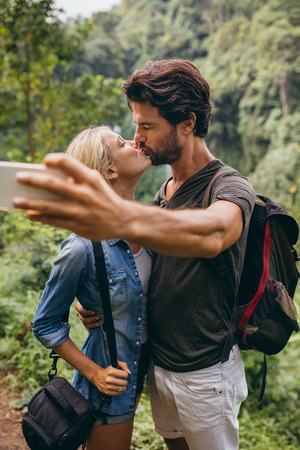 in loving memory: Loving young couple kissing and taking self portrait with their cell phone. Couple in love taking self picture in forest.