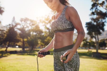 mujer deportista: tiro al aire libre de la deportista joven que salta al aire libre en el parque. femenina aptitud que se resuelve con la cuerda de salto en un día soleado.
