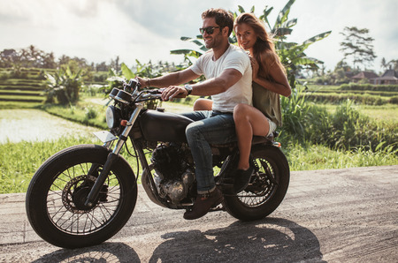 Outdoor shot of happy young couple enjoying motorcycle ride on country road. Man and woman riding motorbike on a summer day.
