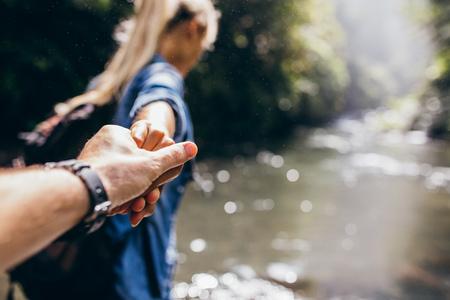 Twee wandelaars in de natuur. Close-up van man en vrouwenholdingshanden terwijl het overschrijden van de kreek. Focus op handen van het paar.
