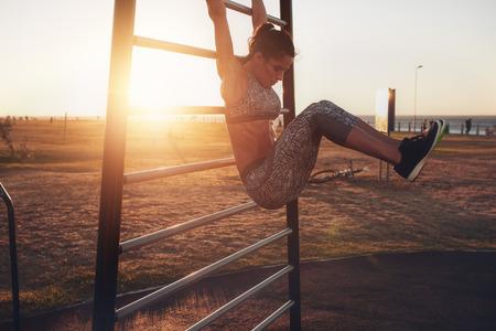 Candid záběr reálného zdravý a fit žena předvádění k zavěšení na noze zvyšuje na venkovní fitness stanici v západu slunce u plážové promenády. Ukazující silné břišní šest-pack.