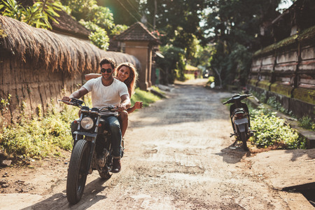 village man: Shot of young couple on motorcycle on country road. Man riding on a motorbike with girlfriend on village road.