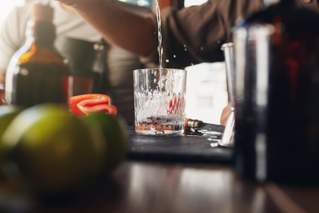 Closeup shot of bartender pouring drink into a glass on counter. Barman preparing cocktail.