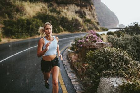 Mulher de fitness correndo na estrada ao redor das montanhas. Atleta feminino treinando ao ar livre durante a chuva. Banco de Imagens