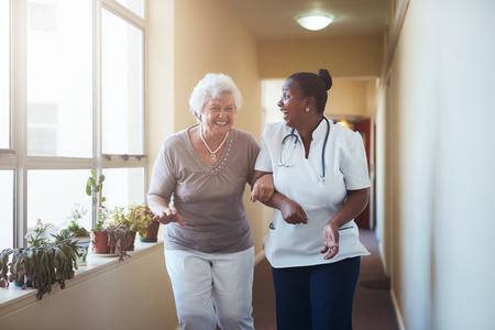 행복 한 의료 작업자와 함께 산책하는 수석 여자의 초상화. 수석 환자와 그녀의 집에 간병인 재미입니다.