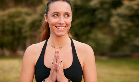 confident woman: Portrait of confident young woman doing yoga looking away and smiling. Fitness female wearing sports bra with her hands joined. Stock Photo