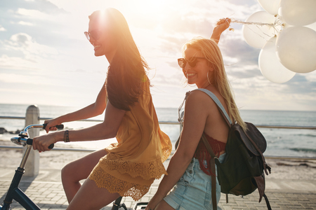 road cycling: Happy young women riding a bicycle together with balloons. Best friends having fun on a cycle by the sea.