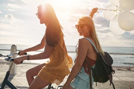 mujeres jóvenes feliz que monta una bicicleta junto con globos. Mejores amigos que se divierten en un ciclo por el mar.