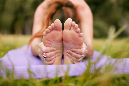 Fitness female sitting on exercise mat bending forward and holding feet. Woman practicing paschimottanasana yoga on grass. Focus on hands holding feet. Stock Photo
