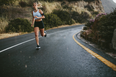 Full length shot of young fitness woman running outdoors on an open highway in countryside.