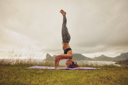 headstand: Full length shot of young woman practicing sirsasana yoga. Fitness woman doing the headstand yoga outdoors on meadow. Stock Photo