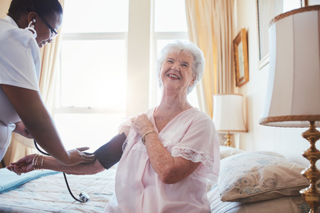 Female doctor measuring blood pressure of senior woman. Elderly woman sitting on bed and smiling while nurse checking her blood pressure. photo