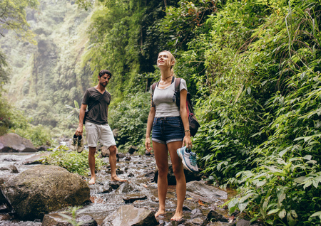 Couple across the stream. Man and woman in forest walking by a creek. Tourist on  nature hike.