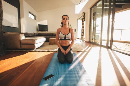 mujer arrodillada: Tiro de la mujer joven en forma practicando yoga dentro. modelo femenino de la aptitud plantean sesión Vajrasana el yoga y la meditación en la estera de ejercicio en casa.