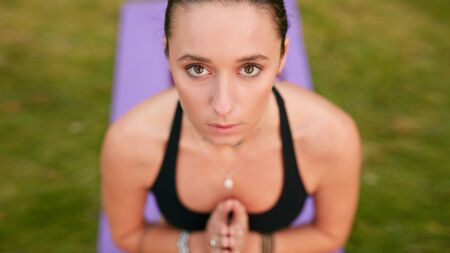 clasped hands: Close up shot of confident young woman meditating with clasped hands and looking at camera. Caucasian fitness female model practicing yoga outdoors.