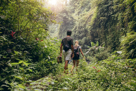 Rear view of young couple walking through woods with their shoes in hand. Man and woman hiking in forest. Фото со стока