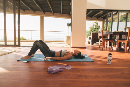 practicing: Shot of fitness woman lying on exercise mat in living room of her apartment. Female relaxing on floor after workout.