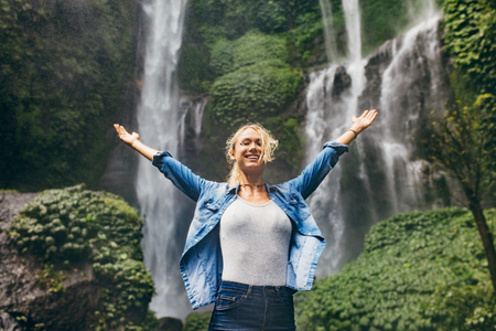 conquering adversity: Happy young woman spreading hands enjoying nature with waterfall in background. Caucasian female standing in front of a waterfall with her arms outstretched.
