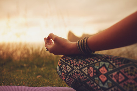 practicing: Close up shot of woman in lotus pose, with focus on hands. Fitness female meditating outdoors during sunset. Stock Photo