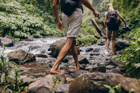 barefooted: Low section shot of man and woman crossing the stream barefooted. Couple walking by the creek in forest with their shoes in hand. Hikers hiking in forest.