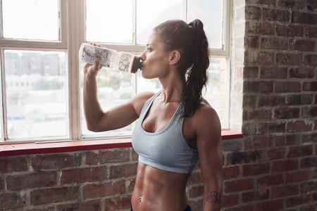 젊은 여자가 마시는 물 체육관에서 맞는. 운동 후 휴식을 취하는 근육 여자.